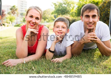 smiling family of three lying on green meadow in town in  summer day