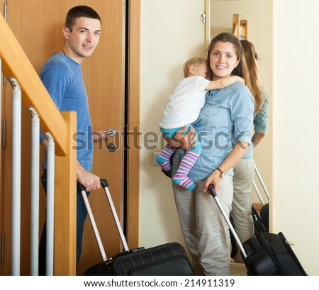 Smiling family of three with child together with luggage leaving the home - stock photo
