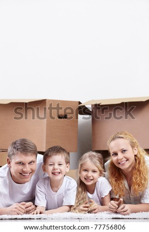 Smiling family on a background of cardboard boxes - stock photo