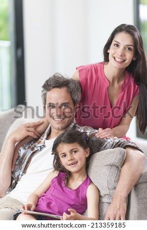 smiling family on a couch looking at camera