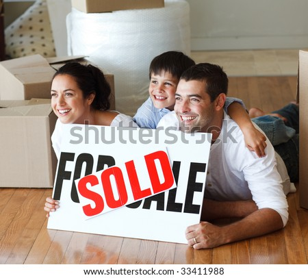 Smiling family on the floor after buying new house