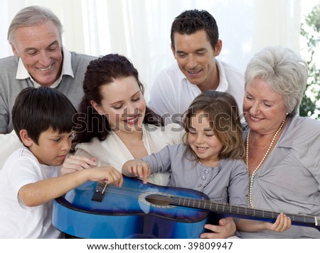 Smiling family playing a guitar in living-room