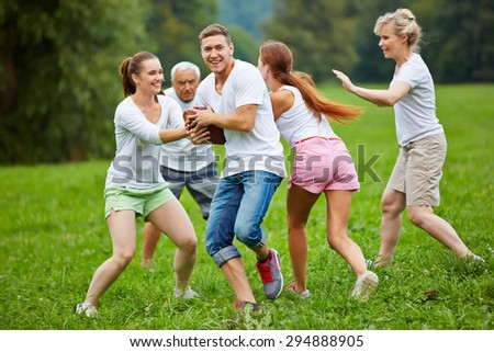 Smiling family playing american football on a meadow in their garden