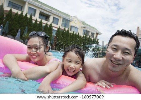 Smiling family portrait in the pool - stock photo