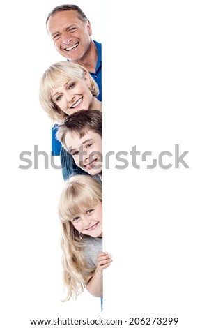 Smiling family posing from behind blank whiteboard - stock photo