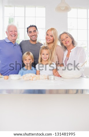 Smiling family posing in the kitchen in front of ustensils - stock photo