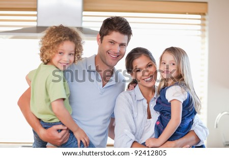 Smiling family posing in their kitchen - stock photo