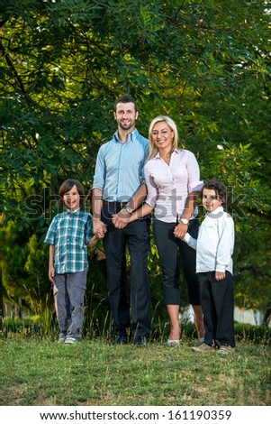 Smiling family posing outdoors in the park - stock photo