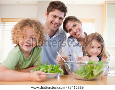 Smiling family preparing a salad together in their kitchen - stock photo
