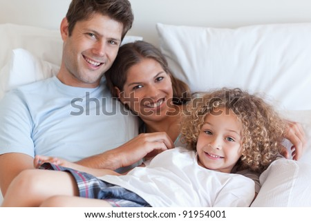 Smiling family relaxing on a bed while looking at the camera - stock photo