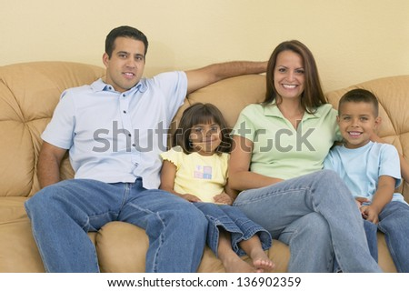 Smiling family relaxing on sofa