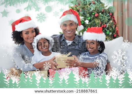 Smiling family sharing Christmas presents against snowflakes and fir trees in green - stock photo