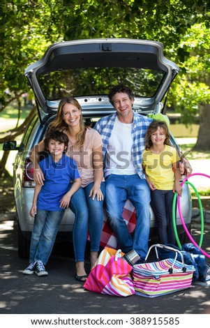 Smiling family sitting in the luggage space of a car