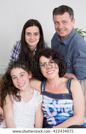 Smiling family sitting on a sofa with lots of love - stock photo