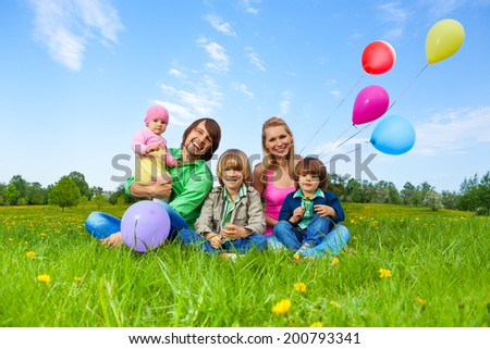 Smiling family sitting on grass with balloons - stock photo