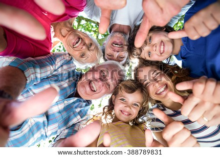 Smiling family standing in a circle with thumbs up - stock photo