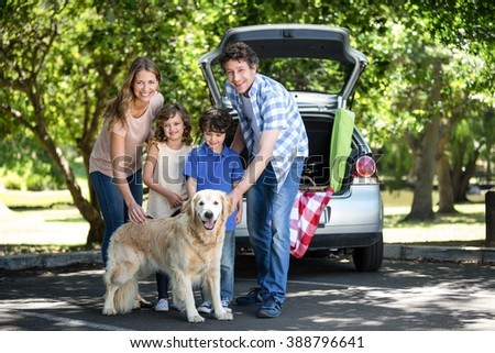 Smiling family standing in front of the car in the garden - stock photo