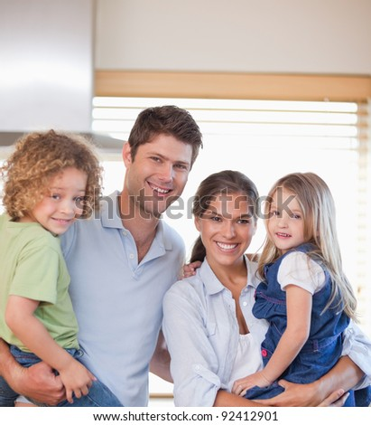 Smiling family standing up in their kitchen - stock photo