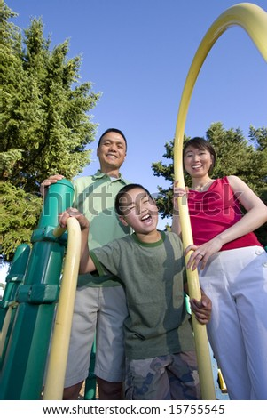 Smiling family stands on jungle gym looking at camera. Boy stands in front making a face at the camera. Vertically framed photo. - stock photo