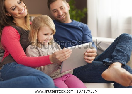 Smiling family using digital tablet at home   - stock photo