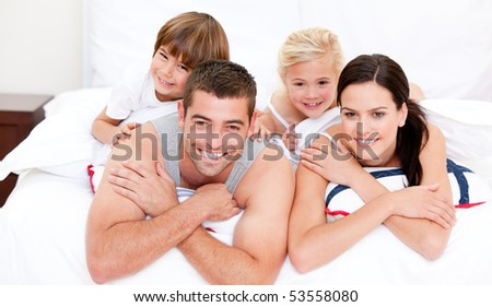 Smiling family waching television at home - stock photo