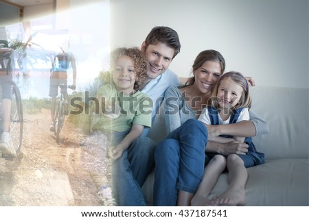 Smiling family watching TV together against fit couple cycling up mountain trail - stock photo