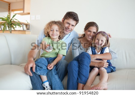 Smiling family watching TV together in their living room - stock photo