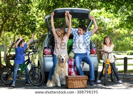 Smiling family with arms up in front of a car - stock photo