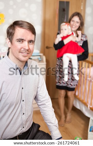Smiling family with baby girl in bedroom together - stock photo
