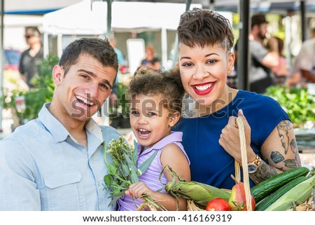 Smiling family with basket of produce at farmers market - stock photo