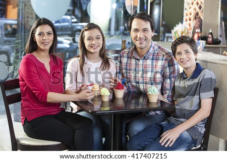 Smiling Family With Ice Creams At Table In Parlor - stock photo