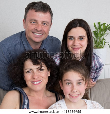 Smiling family with two children at home  - stock photo