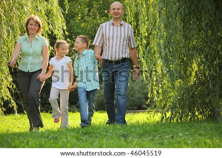 smiling family with two children. father, mother, son and daughter is walking in early fall park.