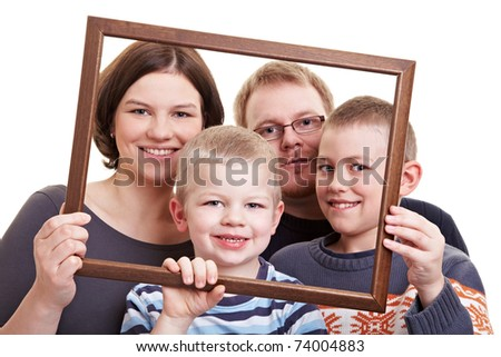 Smiling family with two sons looking through an empty frame