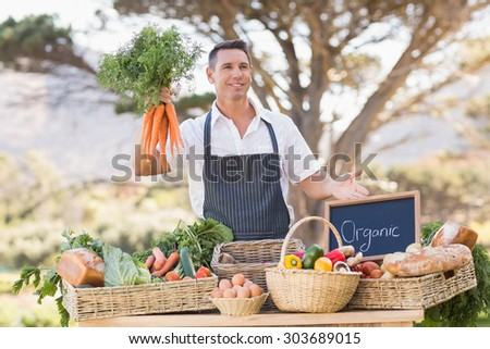 Smiling farmer holding a bunch of carrots at the local market