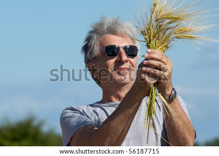 Smiling farmer holding barley in his hands. - stock photo