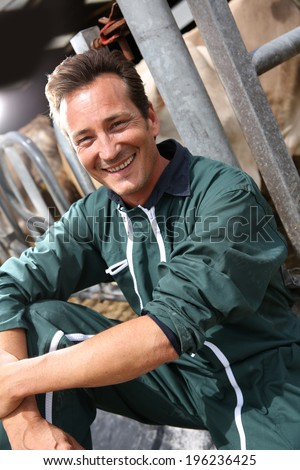 Smiling farmer sitting by cows in barn - stock photo
