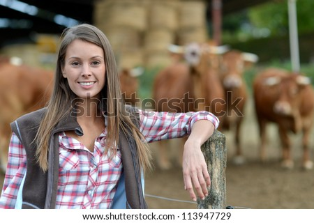 Smiling farmer woman standing by cattle outside - stock photo