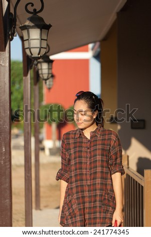 Smiling farmer woman standing by outside her house in farm - stock photo