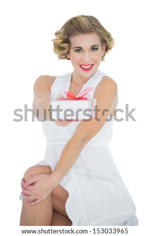 Smiling fashion blonde model offering a gift on white background - stock photo