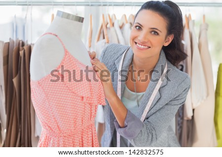 Smiling fashion designer fixing dress on a mannequin in a studio