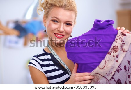 Smiling fashion designer standing near mannequin in office - stock photo