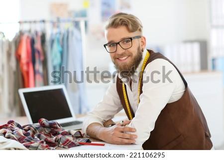 Smiling fashion designer working in studio - stock photo