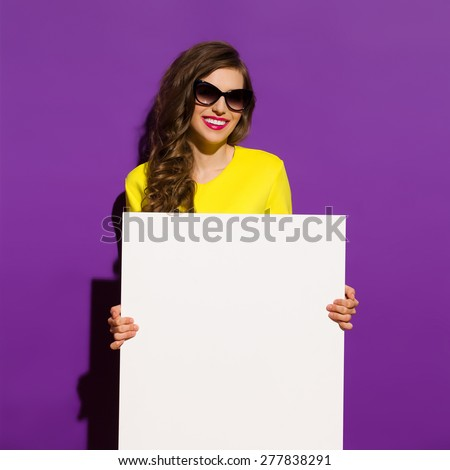 Smiling Fashion Girl Holding White Paper Sheet. Beautiful girl in sunglasses holding a white copy space. Three quarter length studio shot on violet background. - stock photo