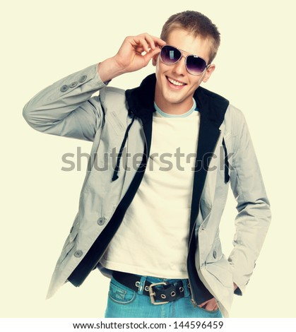 smiling fashion man in sunglasses on light background