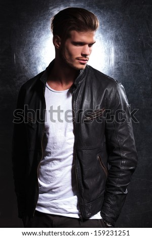 smiling fashion man wearing a leather jacket looking away from the camera, side view picture - stock photo