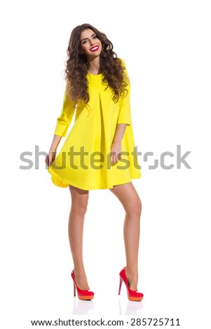Smiling fashion model posing in red high heels and simple yellow mini dress. Full length studio shot isolated on white. - stock photo