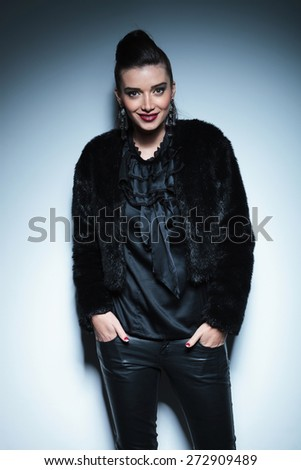 Smiling fashion woman standing on grey studio background with her hands in pockets