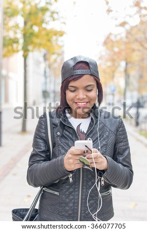 Smiling fashion young woman with headphones listening to music and walking in the street.