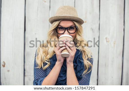 Smiling fashionable blonde drinking coffee outdoors on wooden background - stock photo